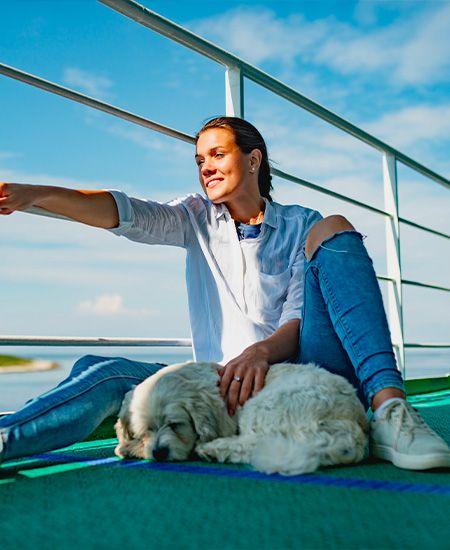 Ragazza sorridente sul ponte di una nave che accarezza un cane bianco