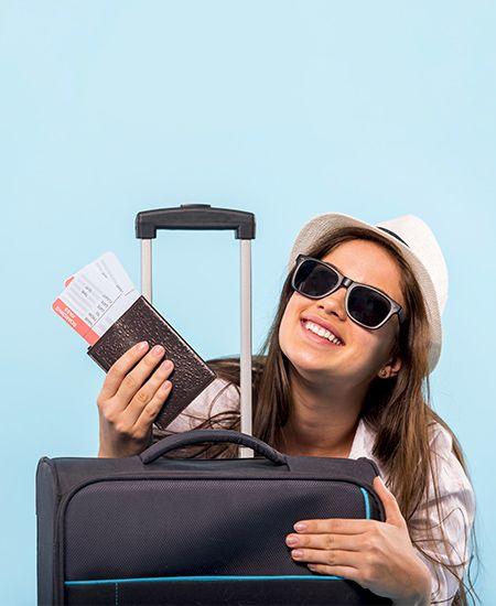 Ragazza sorridente con occhiali da sole e cappello panama bianco che stringe valigia e un portafoglio con biglietti.