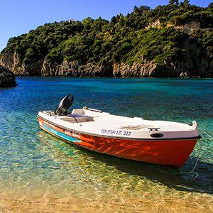 barca sulla riva nel mare cristallino a corfù