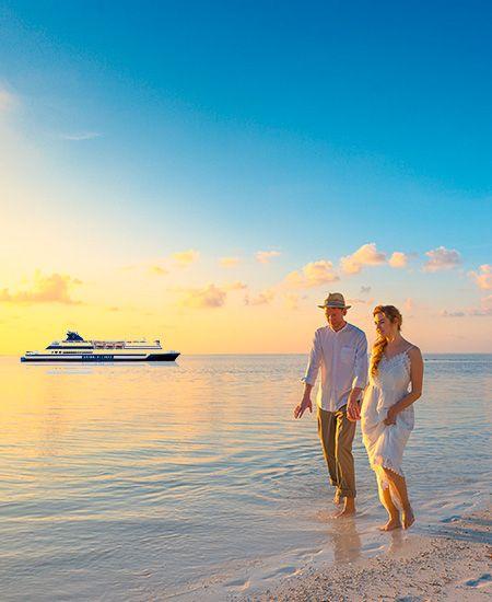 coppia che passeggia sulla spiaggia al tramonto con nave sullo sfondo
