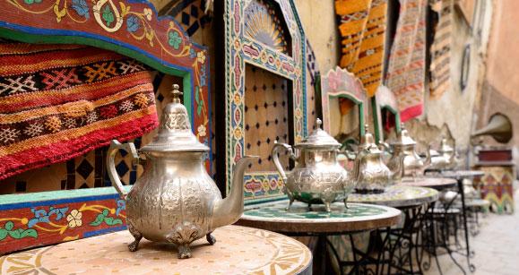 Tipico locale marocchino con tavolini teiere e sullo sfondo dei muri tipici colorati.