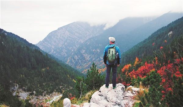 Uomo con zaino e cappello sulla cima di una montagna